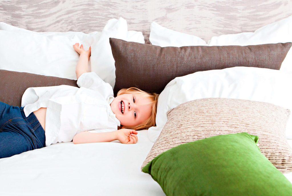 Un niño se divierte jugando sobre el colchón.